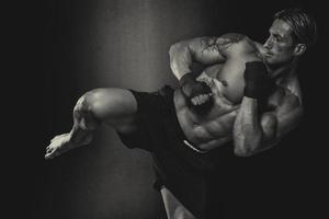 Combattente di mma che pratica alcuni calci con il sacco da boxe