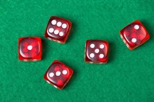 cinque dadi rossi sul tavolo verde foto