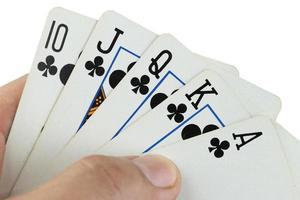 carte da gioco scala reale in mano.