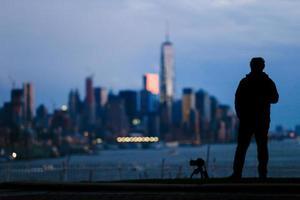 sagoma del fotografo uomo e fotocamera treppiede foto