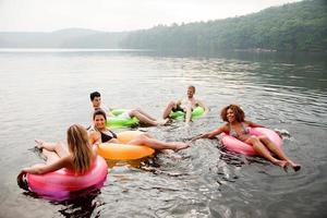amici che giocano in anelli gonfiabili sul lago