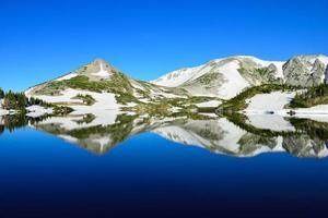 montagne innevate e lago alpino con la riflessione foto