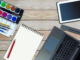 laptop, tablet, quaderno di schizzi, acquarello / concept creativo di attrezzature per ufficio foto