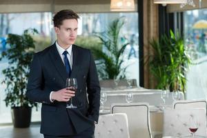 basamento bello dell'uomo d'affari con bicchiere di vino in ristorante foto