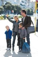 famiglia che aspetta l'autobus foto