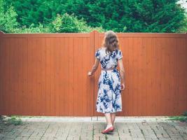 giovane donna che apre cancello arancione foto