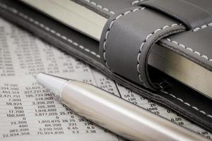 penna appoggiata su figure di valuta mondiale foto