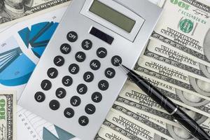penna, calcolatrice e dollari sul primo piano del grafico.