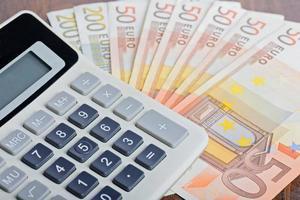 calcolatrice e banconote sul tavolo foto