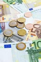 pila di banconote e monete in euro foto