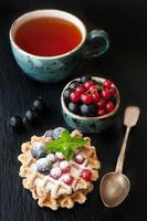 waffle con frutti di bosco e tazza di tè foto