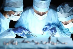 gruppo di chirurghi al lavoro operanti in sala operatoria foto