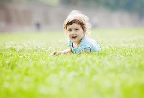 bambino che gioca al prato di erba foto
