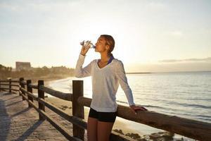 giovane jogger che beve una bevanda energetica foto