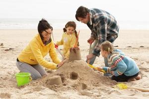 castello di sabbia della costruzione della famiglia sulla spiaggia di inverno foto