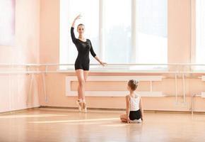 principiante della ragazza che guarda studente di ballo più anziano
