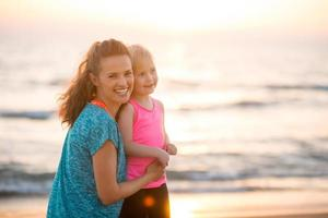 Ritratto di felice madre e figlia sulla spiaggia al tramonto foto