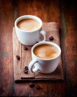 esposizione culinaria di due tazze di caffè espresso con fagioli sparsi foto