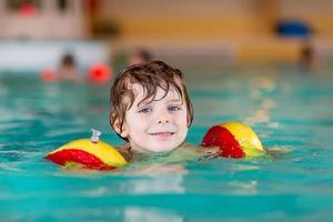 giovane papà che insegna al suo piccolo figlio a nuotare al chiuso foto