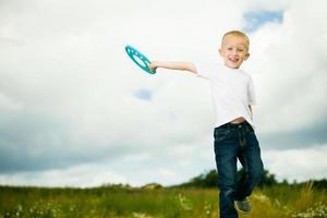 bambino nel parco giochi bambino in azione ragazzo giocando con il frisbee foto