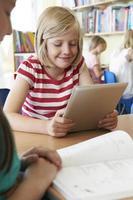 allievo della scuola elementare che utilizza compressa digitale nell'aula foto