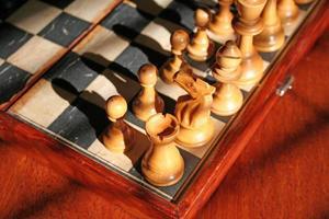 primo piano di pezzi degli scacchi su una vecchia scacchiera in legno foto