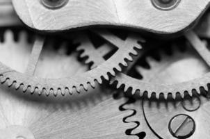 sfondo bianco nero con ruote dentate metalliche un orologio. macro
