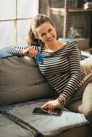 felice giovane donna con carta di credito utilizzando tablet pc