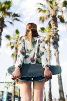 donna elegante con penny board in piedi contro il cielo tropicale
