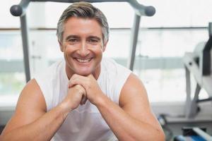 uomo adatto che sorride alla macchina fotografica nello studio fitness foto