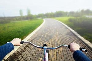 donna in sella a una bicicletta nel parco, vista sul manubrio. foto