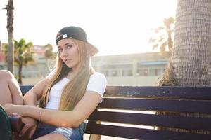 skateboarder alla moda della donna che si rilassa dopo avere guidato sul bordo del penny foto