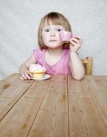 atteggiamento tea party - ragazza con tazza rosa e cupcake foto