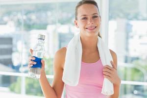 donna con asciugamano e bottiglia d'acqua in palestra foto