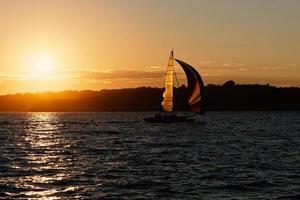 nave a vela al tramonto.