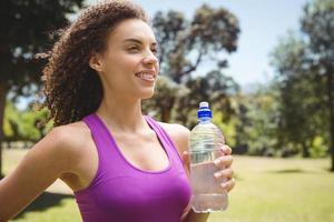 donna adatta che tiene bottiglia d'acqua