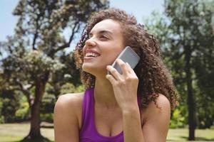 donna adatta al telefono nel parco foto