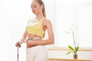 dieta. concetto di dieta. donna in abiti sportivi che misura la sua vita foto