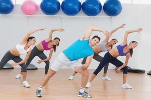 classe facendo esercizio di stretching in palestra foto