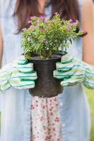 donna felice che tiene i fiori in vaso foto