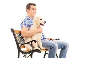 giovane uomo seduto su una panchina con un cucciolo foto