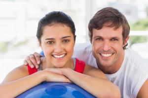 coppia sorridente in forma con palla esercizio in palestra foto