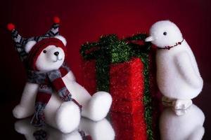 regalo di Natale orso polare e un pinguino su uno sfondo rosso foto