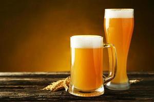 bicchiere di birra su uno sfondo di legno marrone foto