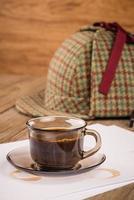tazza di caffè, fogli di carta e cappello da detective foto