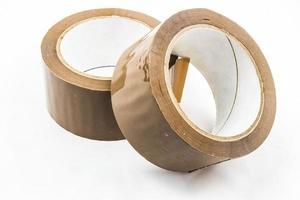 rotolo di nastro adesivo marrone appiccicoso su sfondo bianco foto