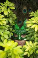 ragazza in maschera con un picco tra le foglie verdi foto
