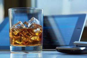 whisky con ghiaccio, tablet e telefono sul tavolo foto