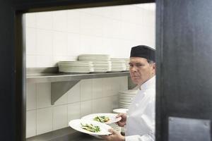 chef maschio con piatti di cibo in cucina foto