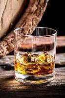 bicchiere di whisky e vecchia botte di rovere